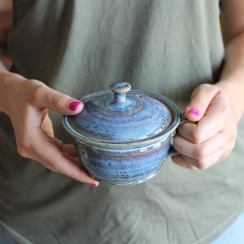 Model holding rustic blue small pot-shaped cooker