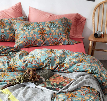 the bed with pink sheets and a blue printed duvet and matching pillows