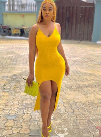 model wearing the yellow v-neck dress with a front curved slit
