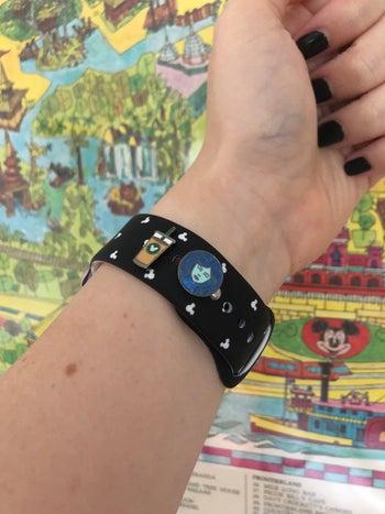 editor's wrist wearing an apple watch with a charm of ice coffee and madame leota