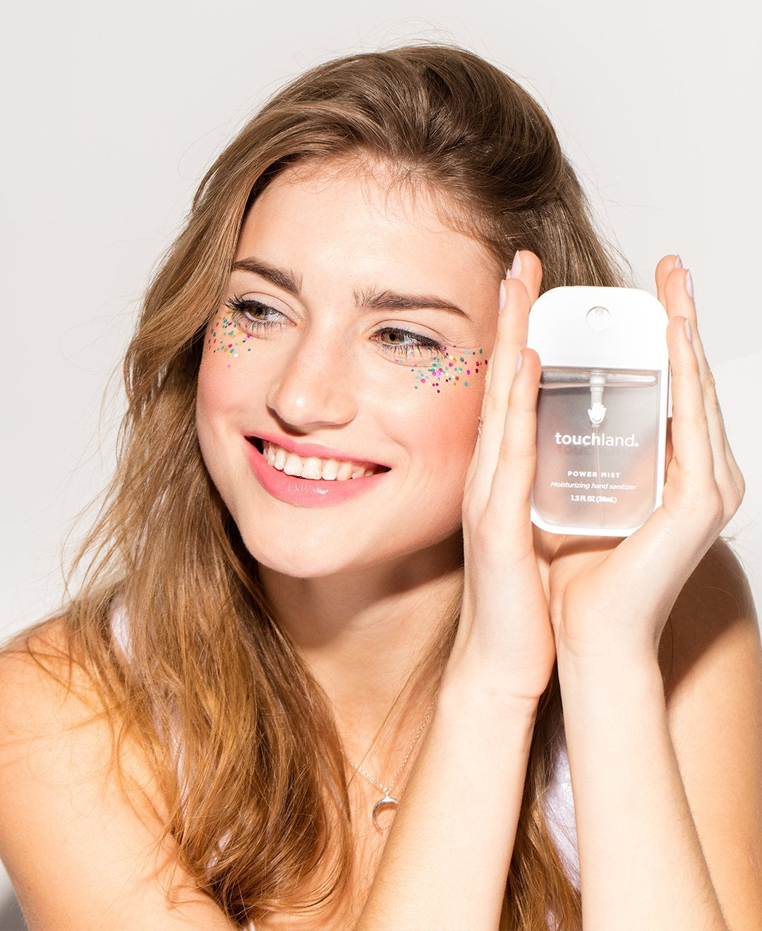 model holding Touchland unscented hand sanitizer