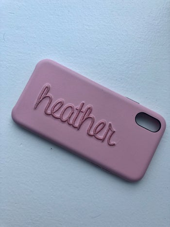buzzfeed editor's phone case in oink with their name on it