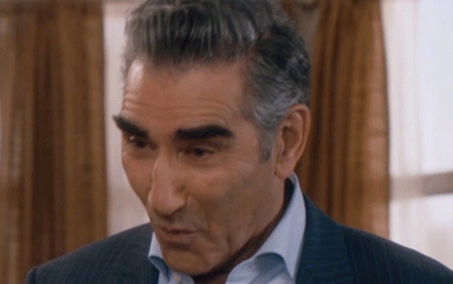 A man with thick eyebrows is leaning his head forward, with his mouth in a small O shape
