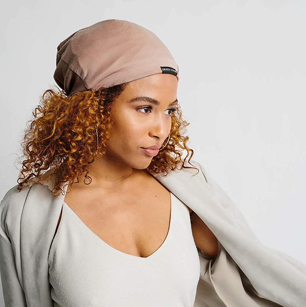 model with thick curly hair wearing the taupe-colored cap, which looks like a beanie