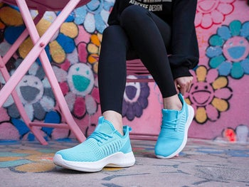 Model sitting while wearing blue SDolphin sneakers