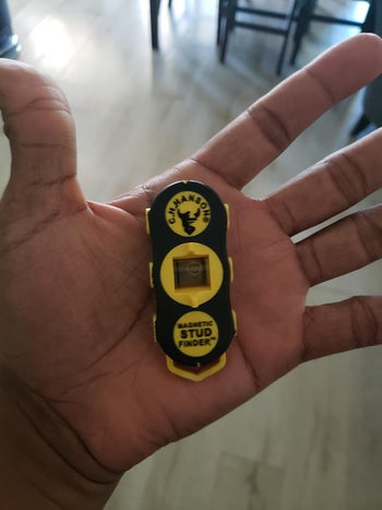 a stud finder in a reviewer's hand, it fits in their palm