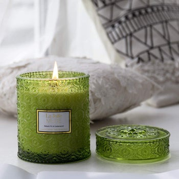 an evergreen candle in a green decorative jar