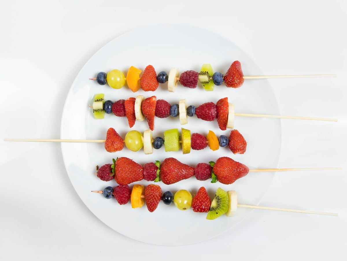 Fruit skewers with grapes, kiwi, blueberries, strawberries, raspberries, melon, and bananas