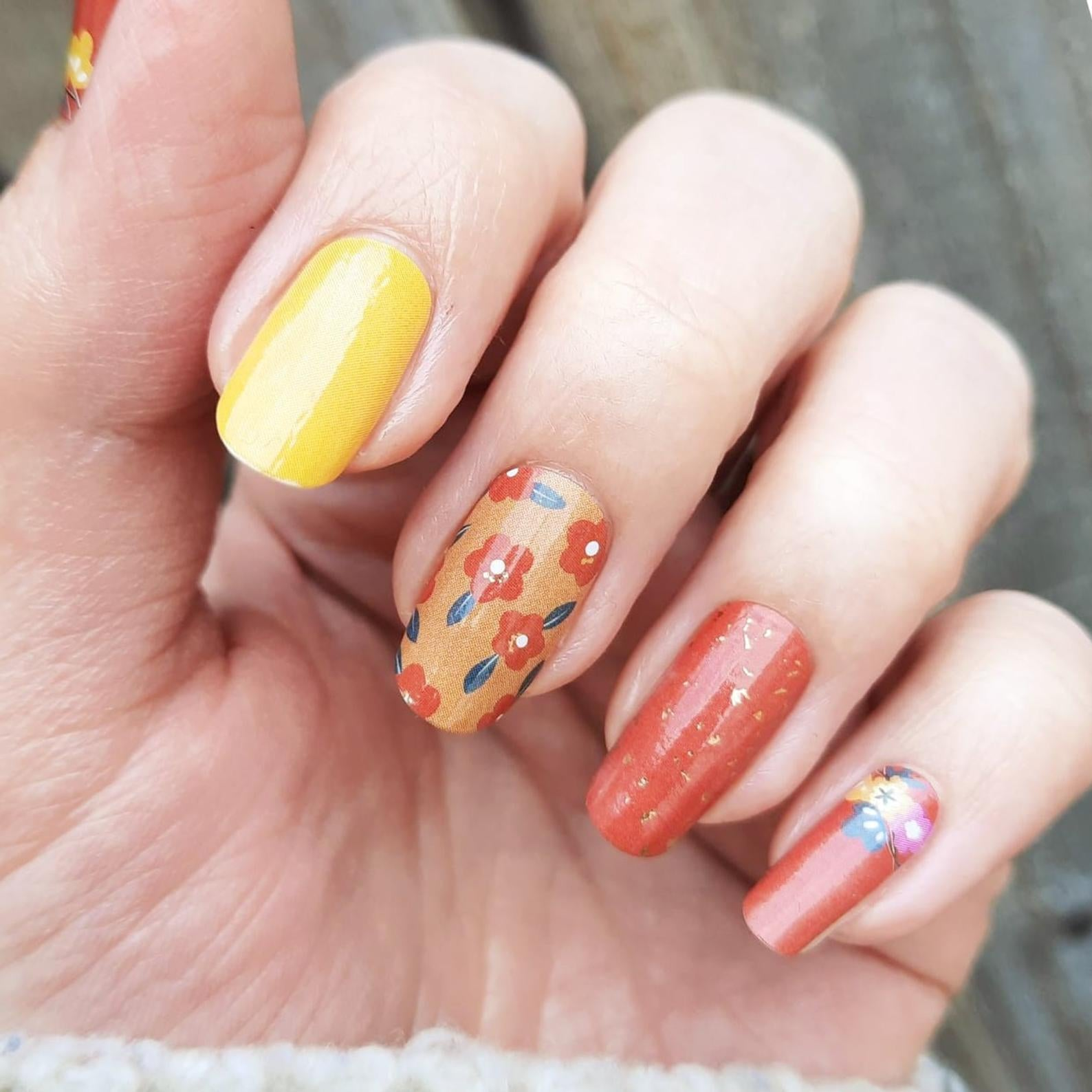 hand wearing nail wraps with a 70s mod style, like orange flowers, yellow, and deep orange