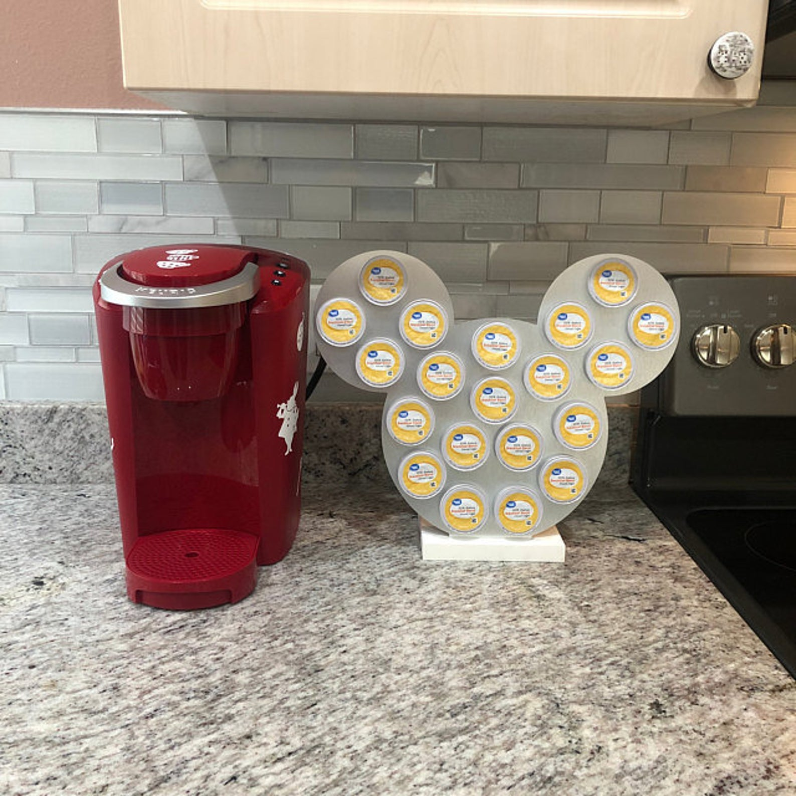 a silver mickey-shaped k-cup holder next to a keurig machine