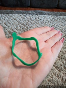 Reviewer holding a green bracelet toy in their palm