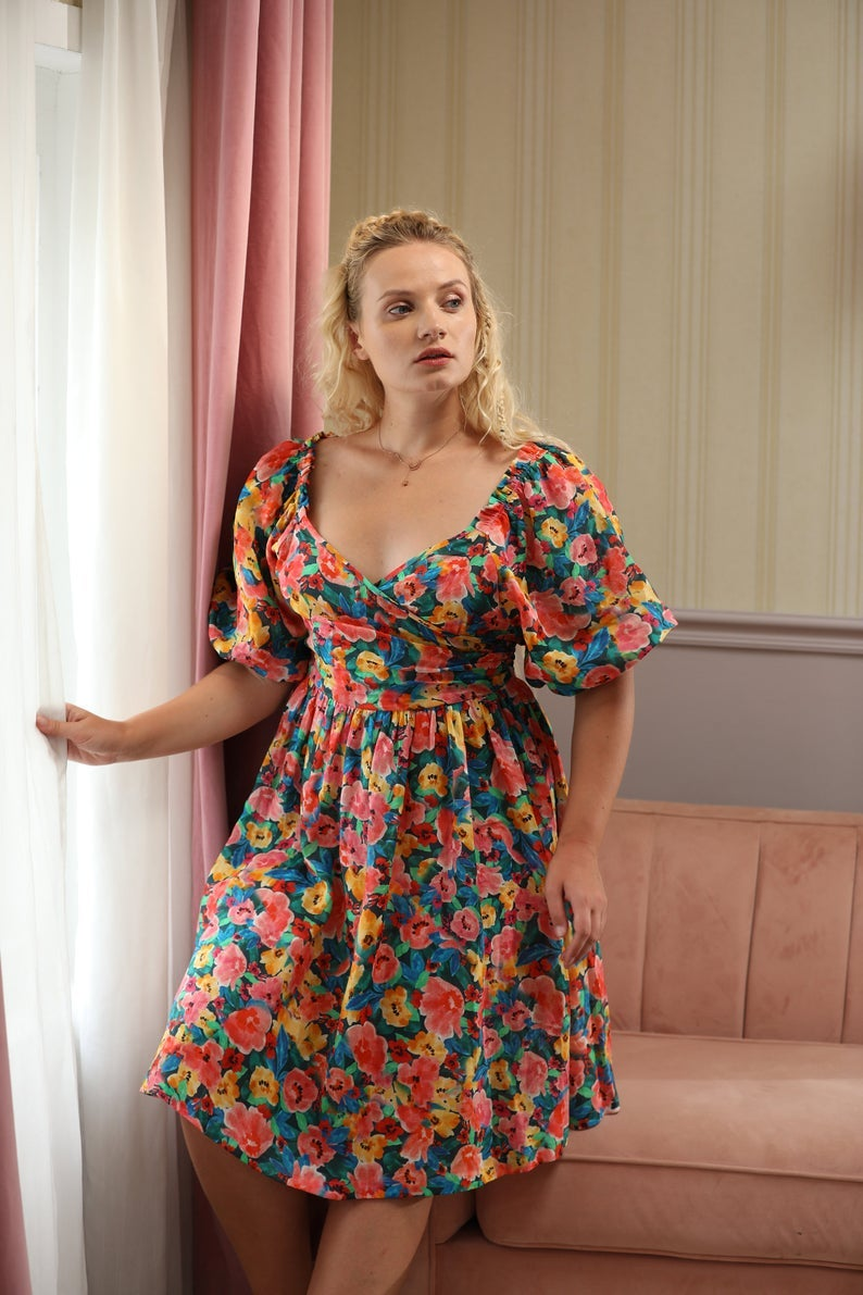model in the pink, green, blue, yellow, and red floral dress