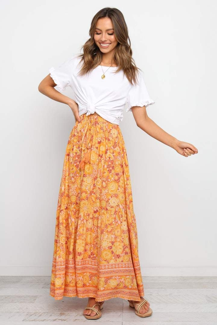 a model in a maxi skirt with an orange boho pattern on it