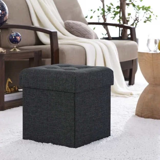 The ottoman in a dark grey color in a living room