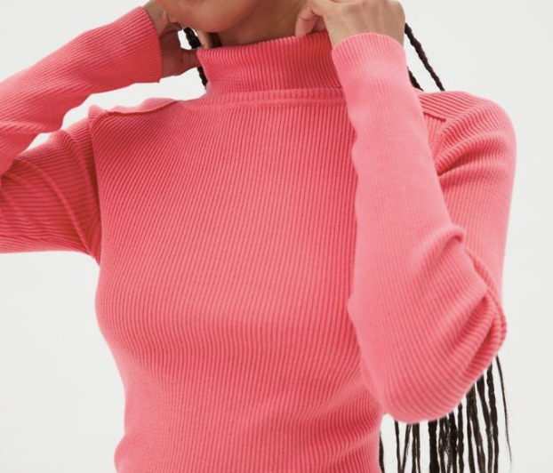 A tight, long-sleeved hot pink turtleneck sweater