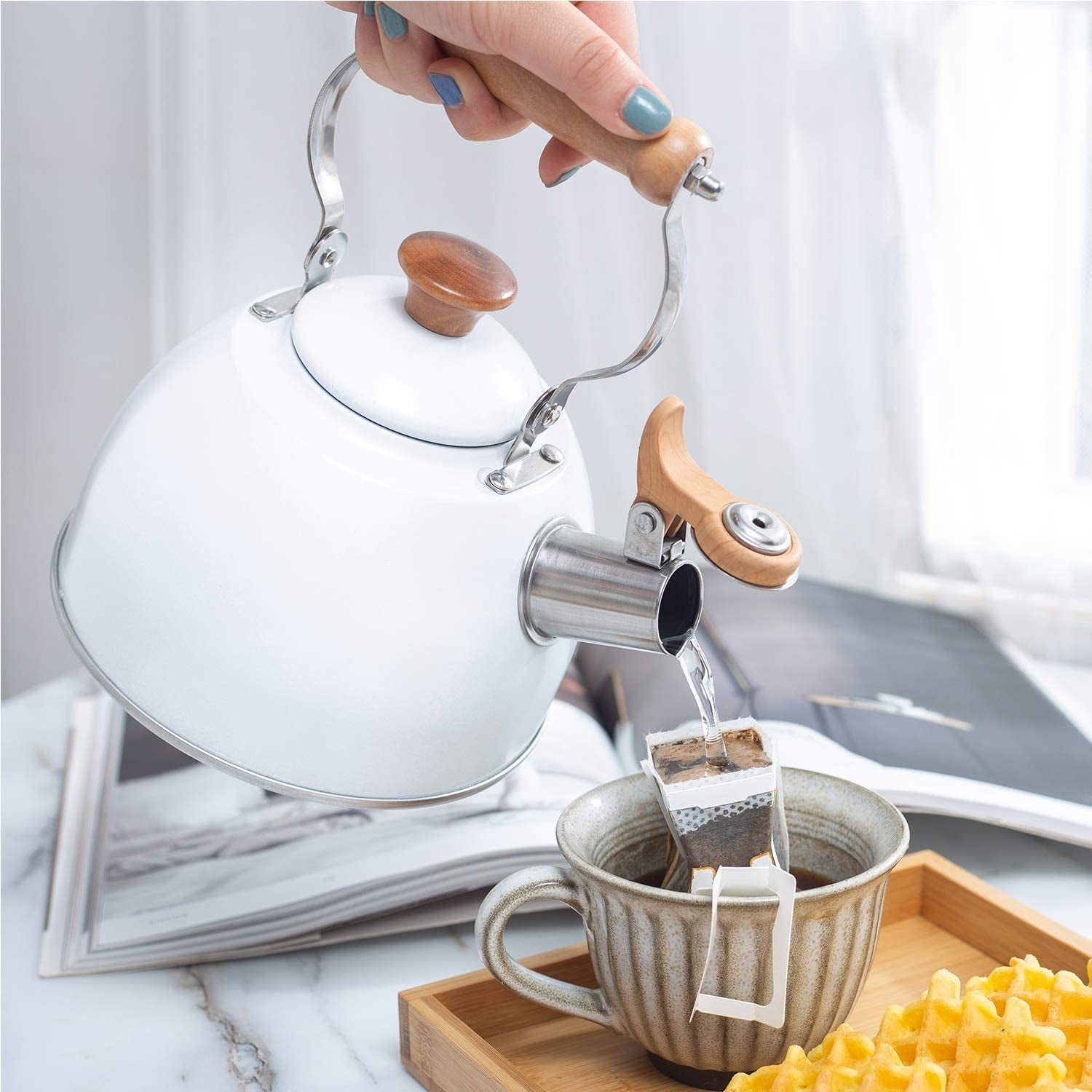 a model pouring hot water from a white kettle