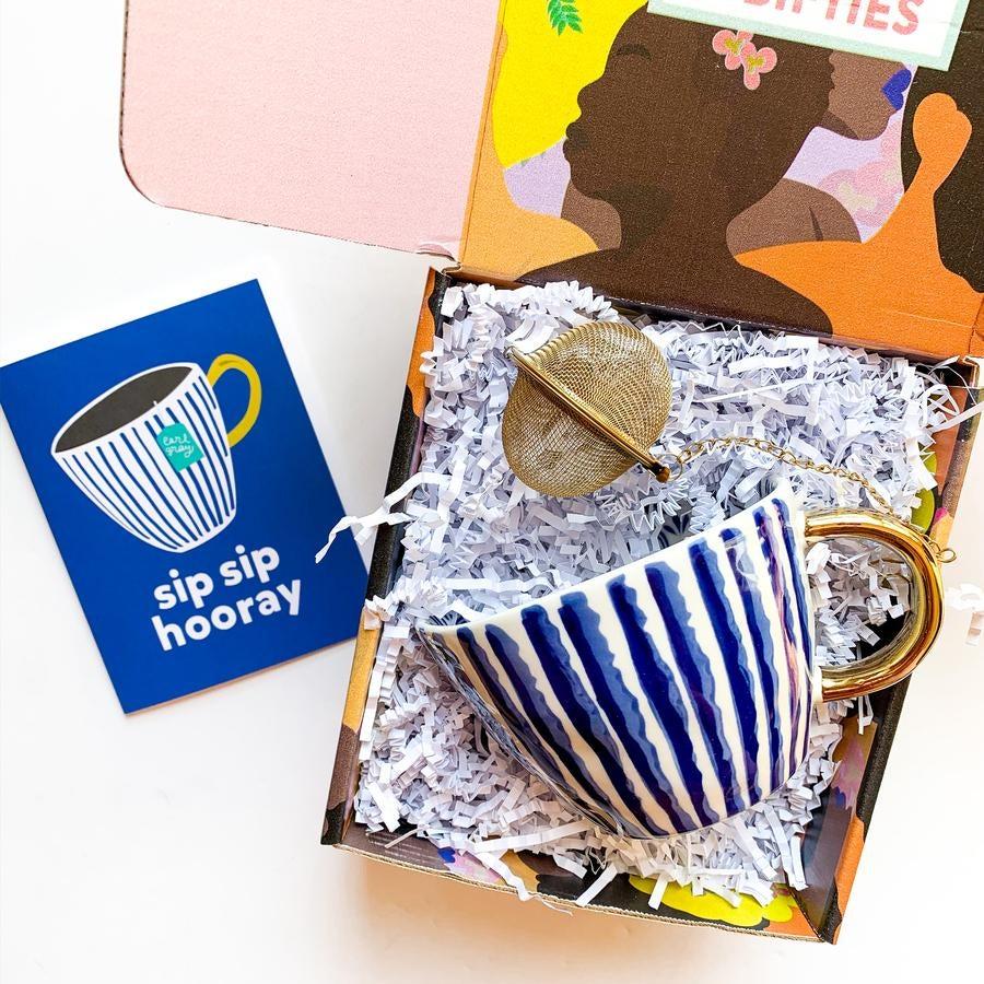 a box with a pretty mug, tea diffuser, and card that says