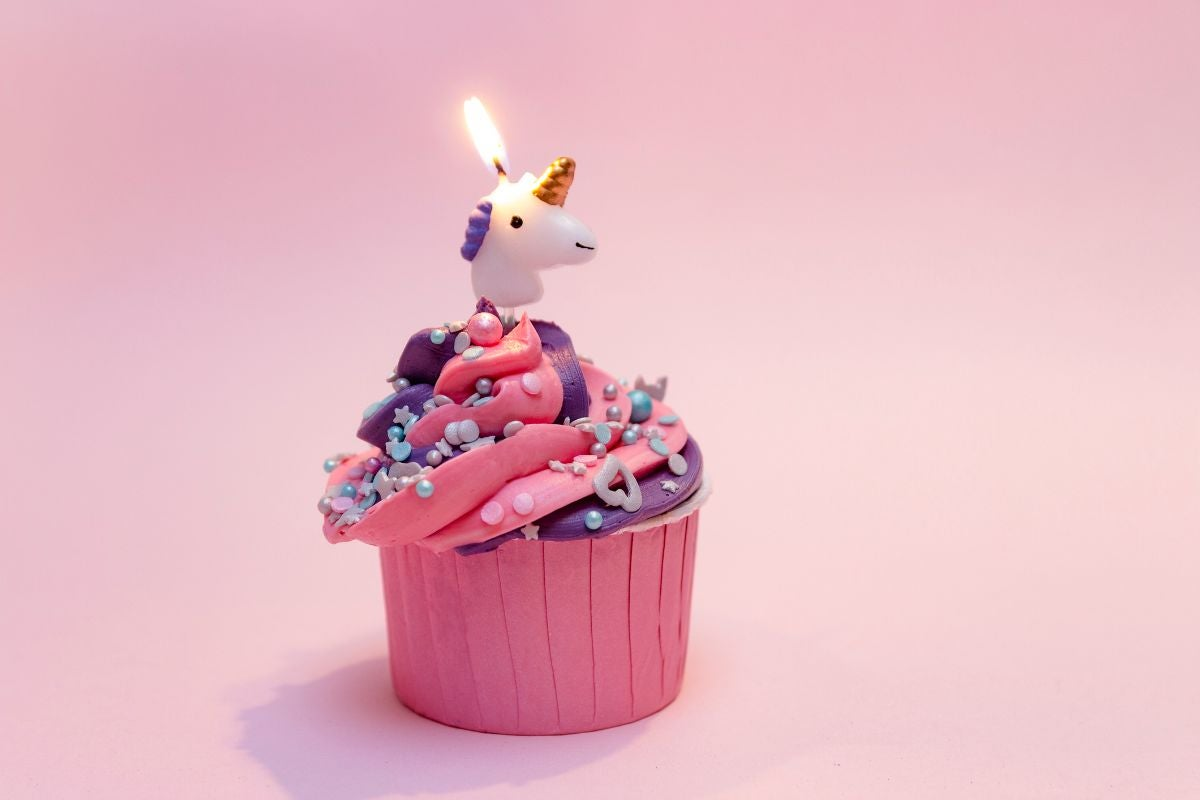 A fun cupcake with sprinkles on top and a unicorn candle