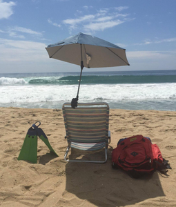 Reviewer image of umbrella clamped to a plastic chair on a beach