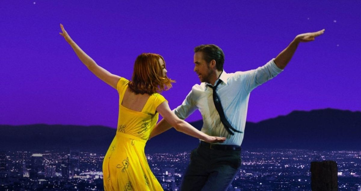 A woman wearing a dress dances with a man wearing a button down shirt and tie