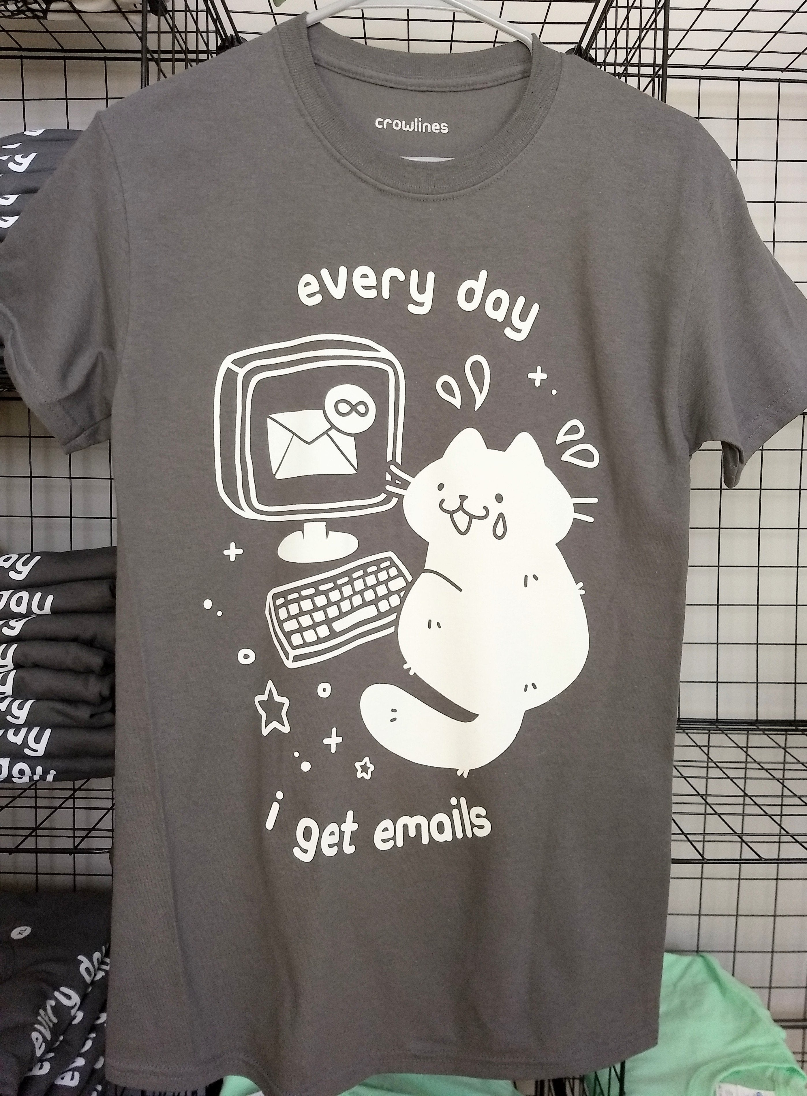 gray short sleeve tee with a white graphic of a cat with a tear on its face in front of a laptop showing inbox infinity and the text