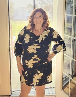 plus-size reviewer wearing the dress in black with white florals