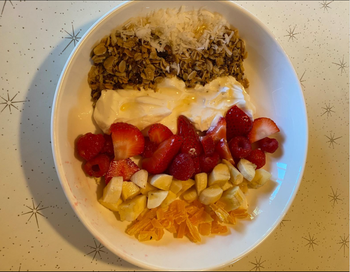 Shallow white bowl plate with fruit and yogurt and granola