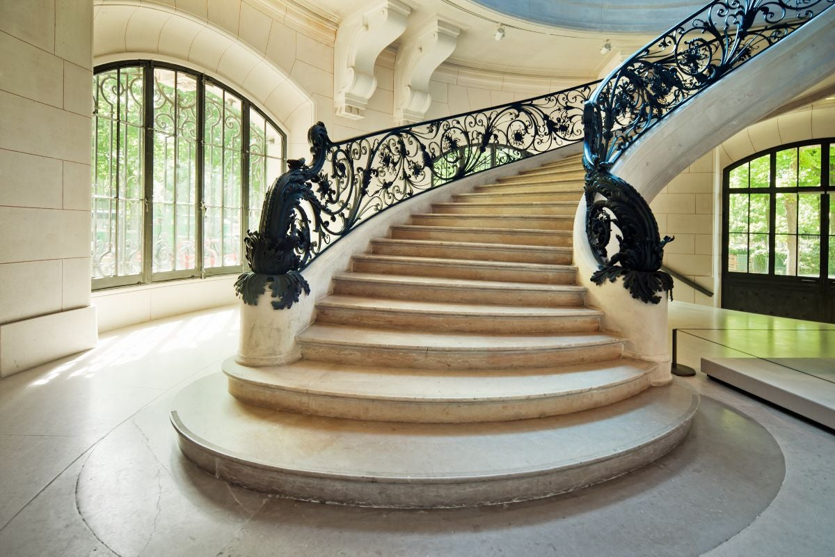 A marble staircase with delicate iron handrails