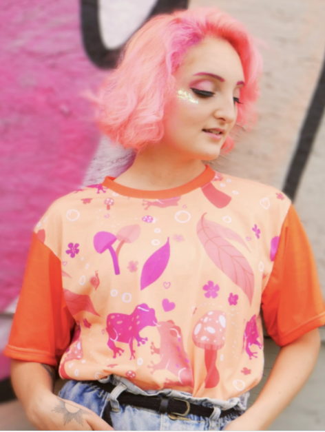 model wearing the orange and hot pink tee with frogs, flowers, leaves, and mushrooms