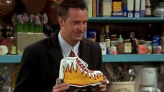 Chandler is holding a shoe design in his hand while standing in the kitchen