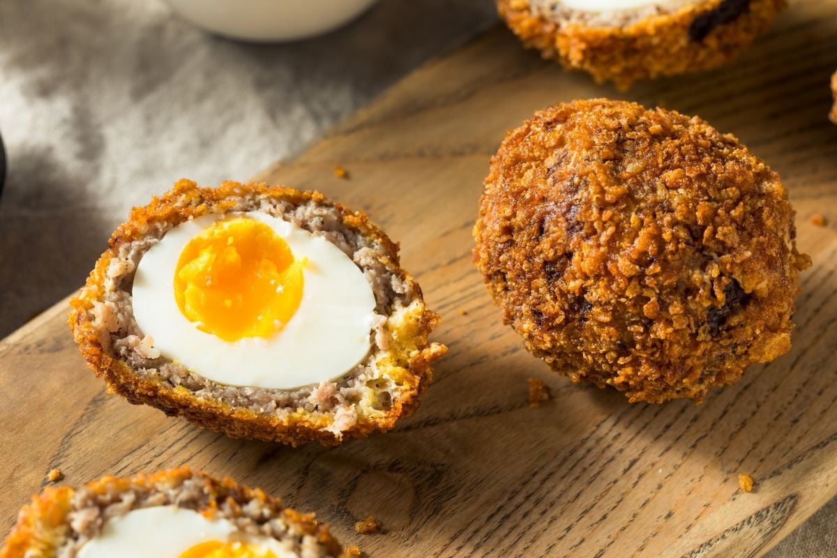A scotch egg cut on half to reveal the egg and yolk on a wooden board