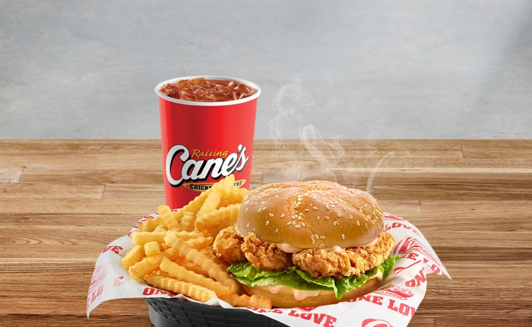 A fried chicken sandwich with crinkle fries and a drink