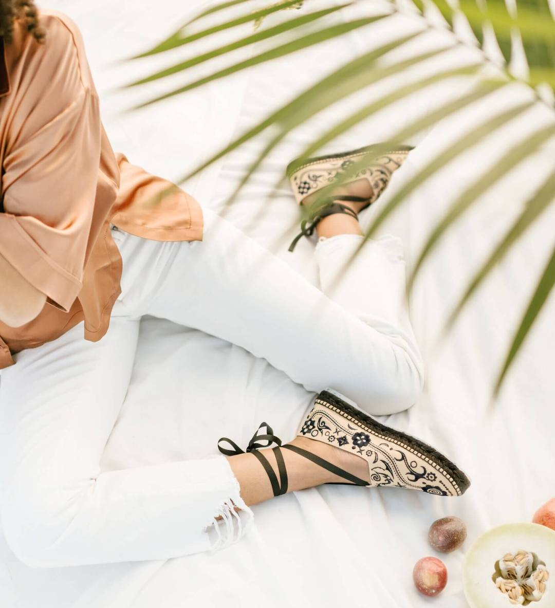 model wearing the closed-toe espadrilles in tan with black illustrations all over them, a black sole, and black laces wrapped around the ankles