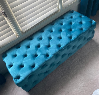 a reviewer photo of the ottoman sitting beneath a window