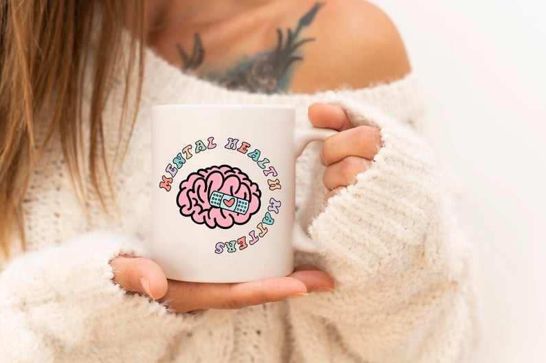 model holding white mug with pastel writing and an illustration of a brain with a heart bandage on it