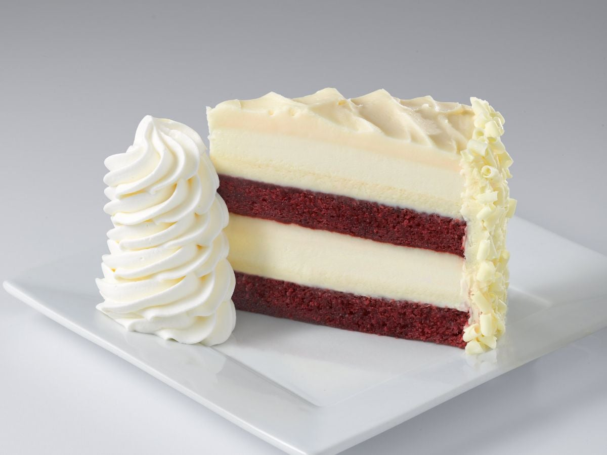 Layers of red velvet cake and cheesecake with white chocolate curls
