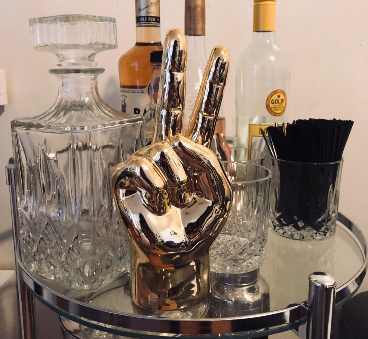 a reviewer photo of a golden peace sign hand statue sitting on a bar cart