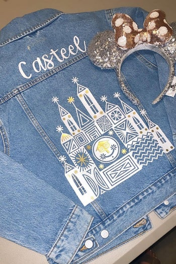 the back of a denim jacket that has a name on it and the it's a small world structure