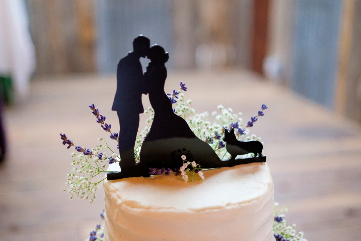A silhouette cake topper of a bride and groom and a corgi