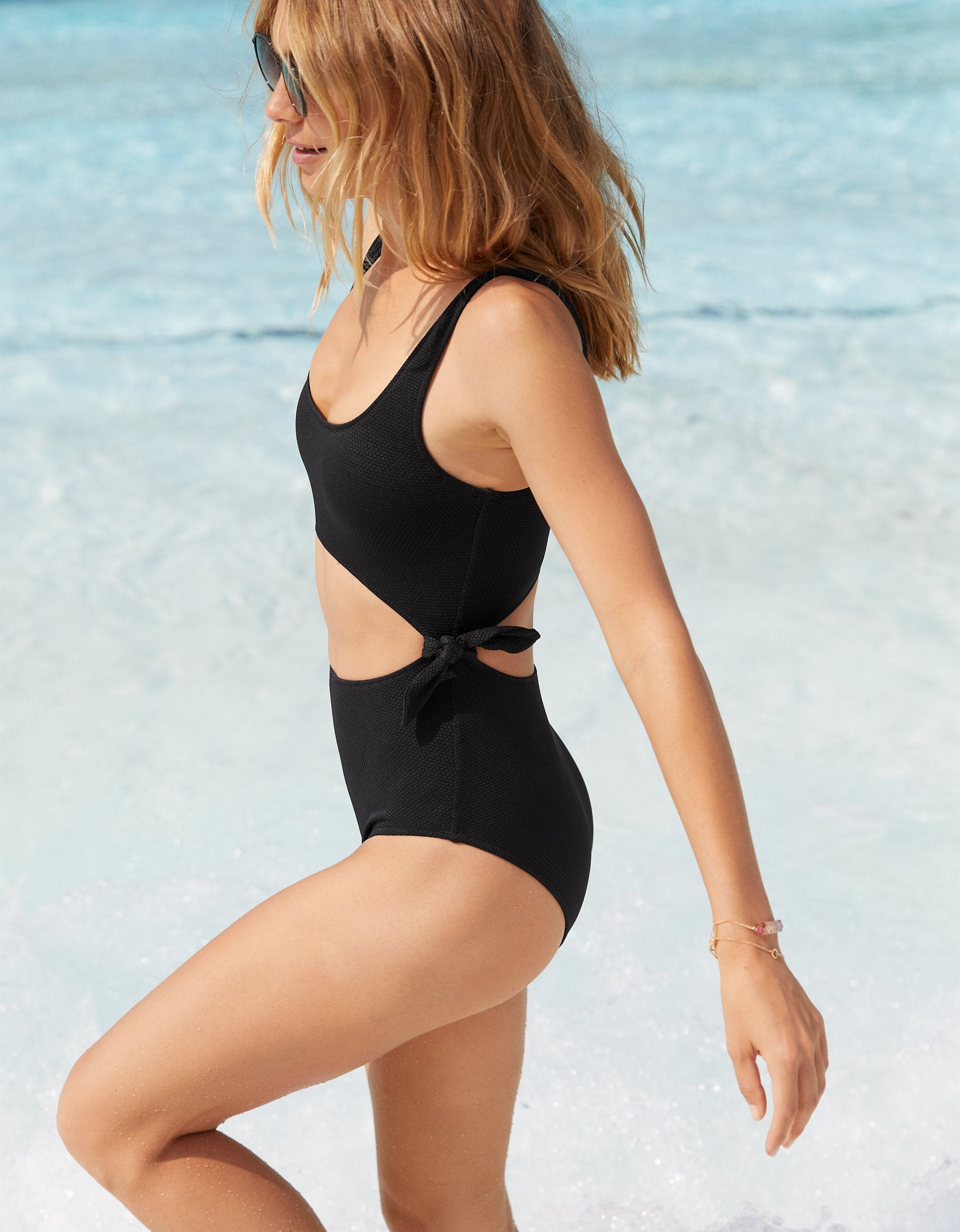 A model in the black one piece with open front and back and ties at the sides