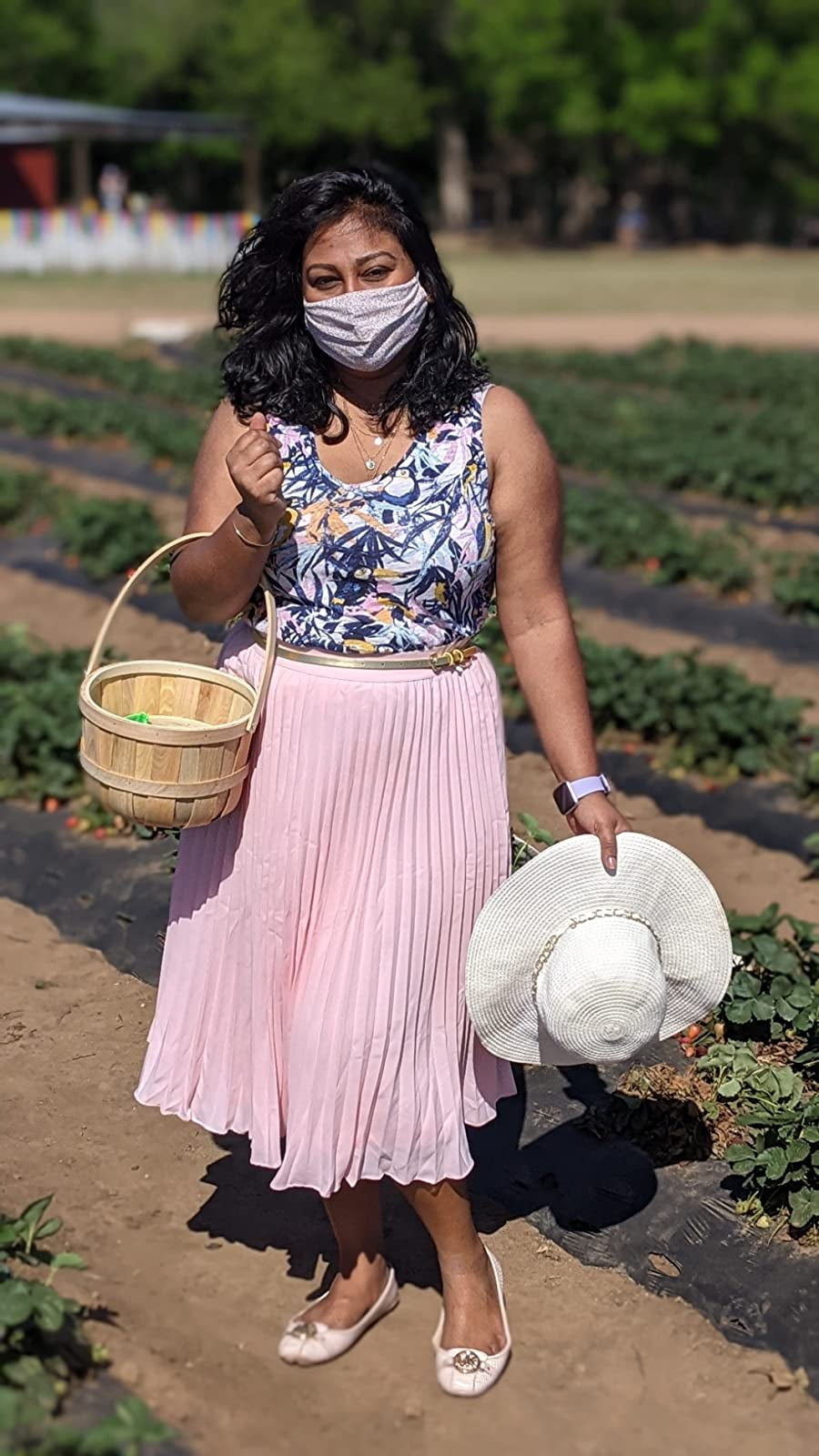 reviewer in pink A-line skirt and floral tank walking on a farm