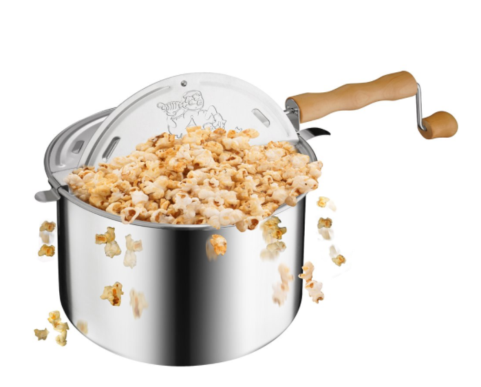A metallic popcorn popper with popcorn flying out of it.