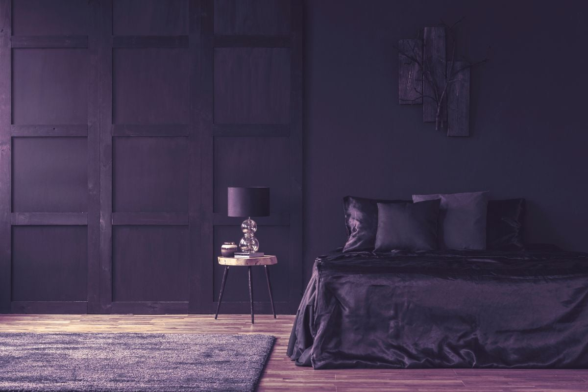 A very dark, royal bedroom with wooden walls, a tiny table lamp, and a plush rug