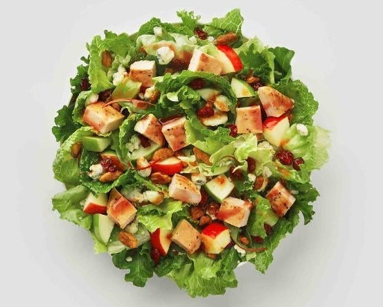 A salad with red and green apples, dried cranberries, roasted pecans, blue cheese crumbles, and grilled chicken
