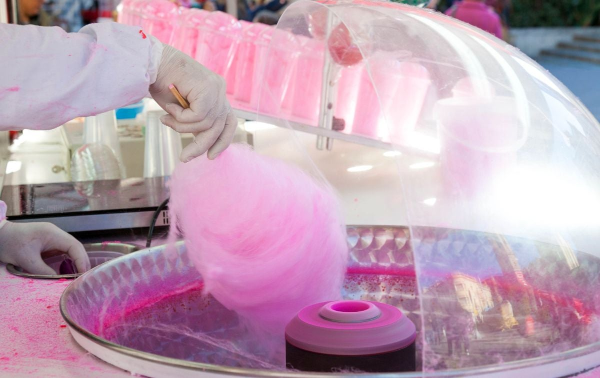 A girl making pink cotton candy in a cotton candy machine