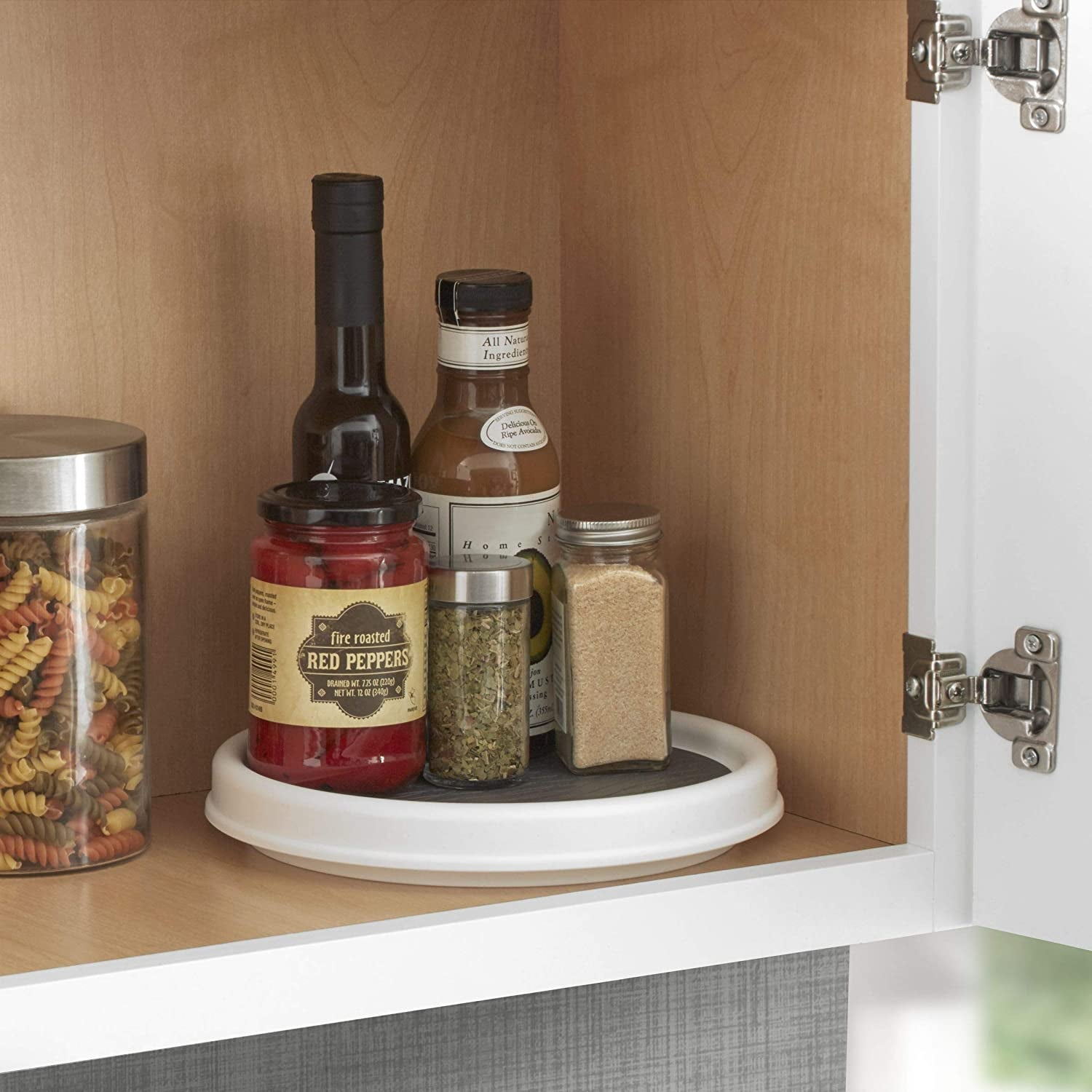 White lazy susan with rubber gripper in pantry with spices on it