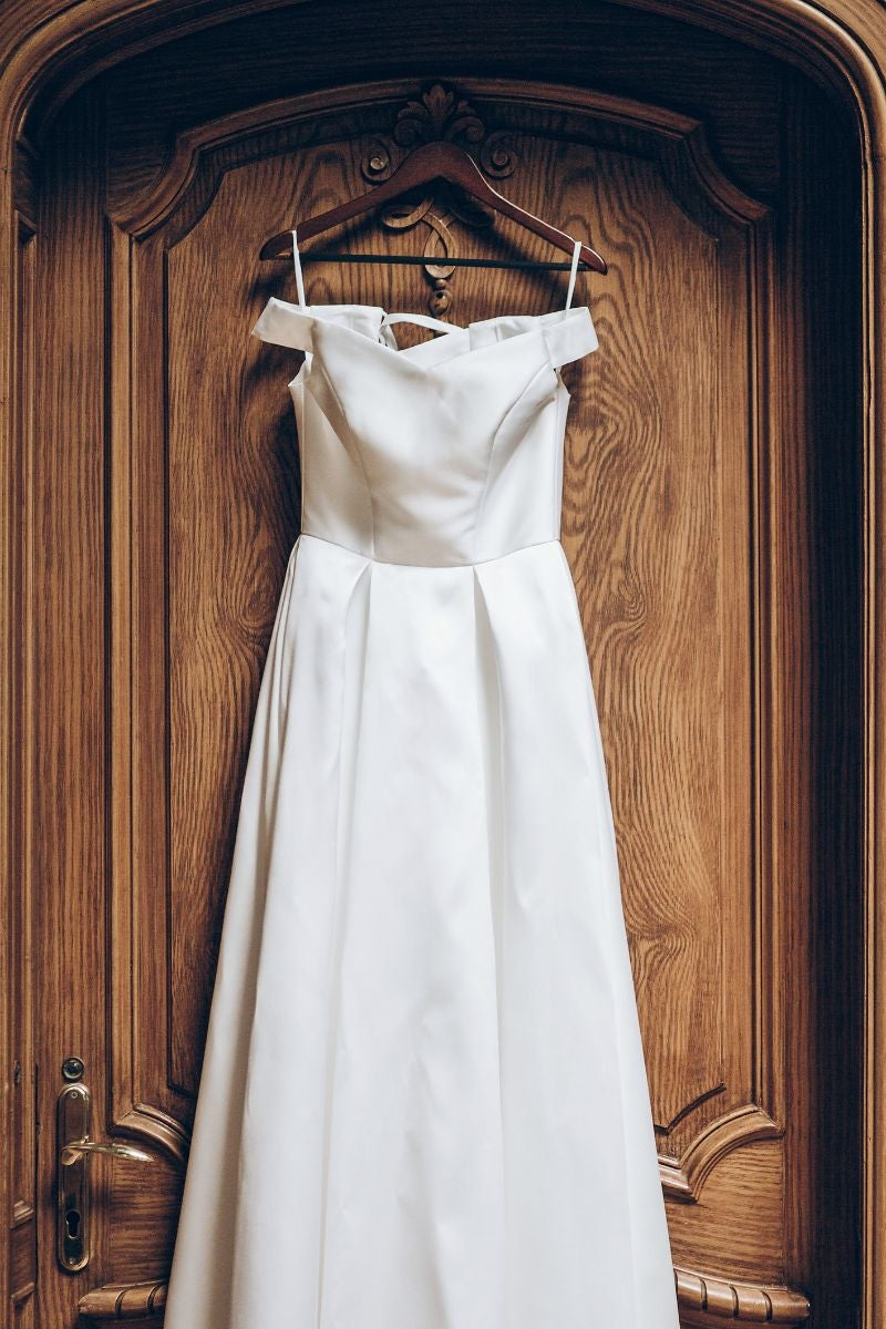 A simple silk wedding dress with an off the shoulder neckline