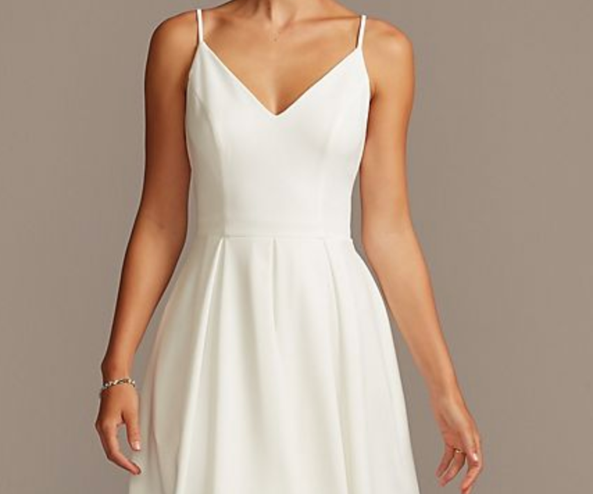 A short wedding dress with thin straps that is tight on the top and flowy on the bottom
