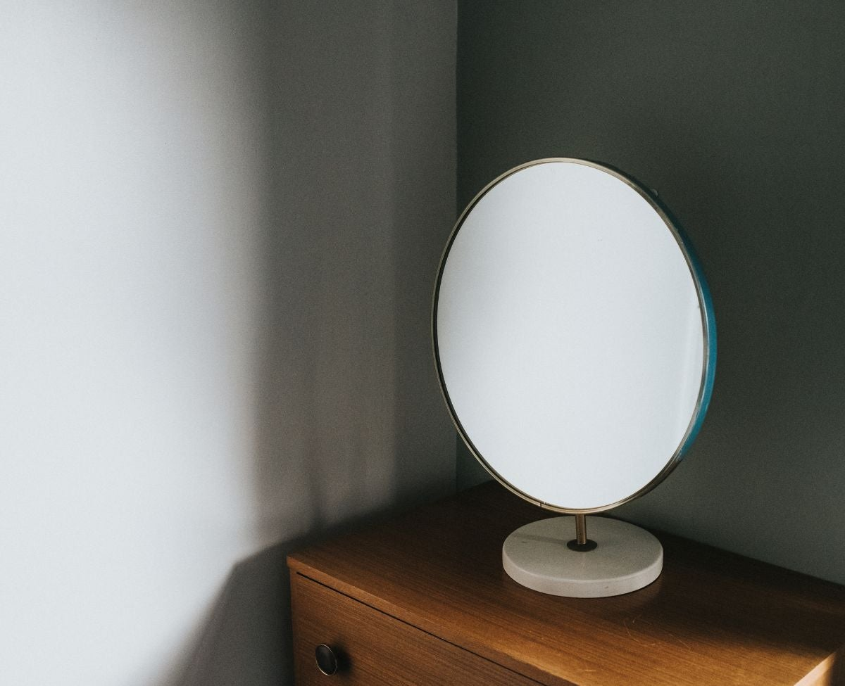 A round makeup mirror on a desk