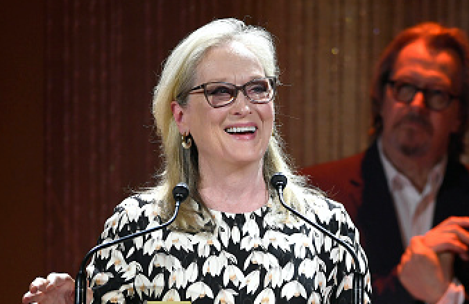 A woman with gray hair and glasses stands at a podium